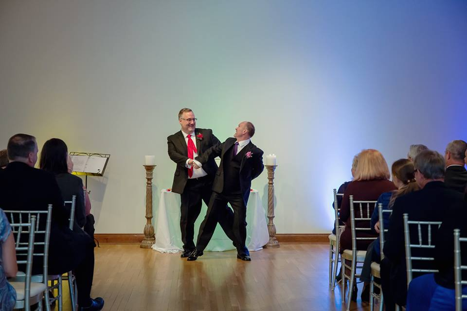 2 men dancing together in large hall.